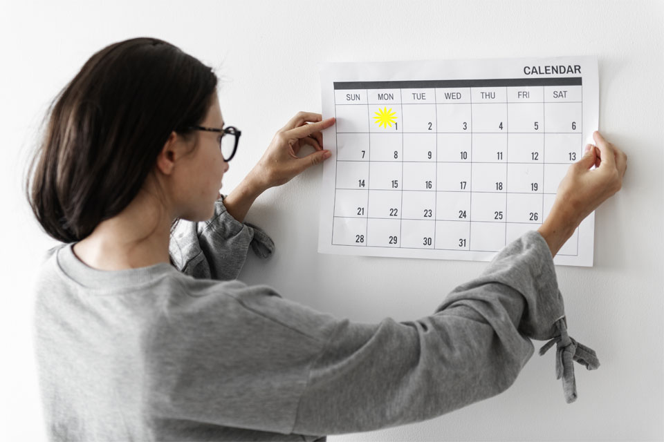 In the calendar this woman is looking at, the 1st is highlighted - is she thinking about new resolutions for her business?