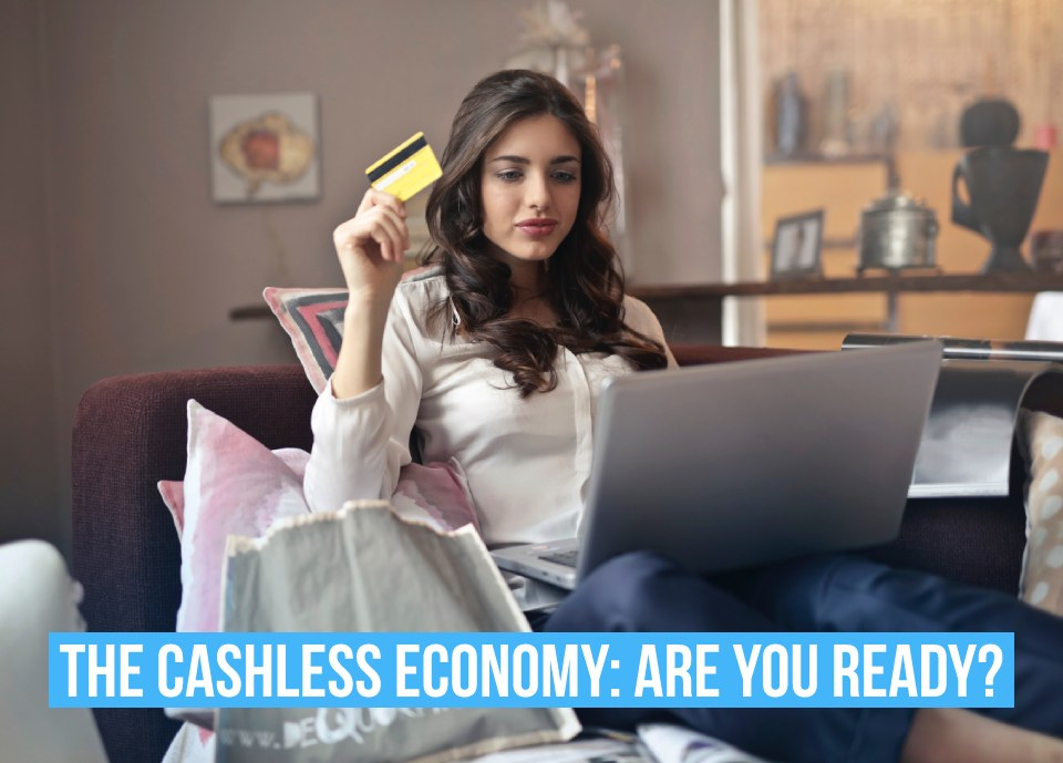 A women holiday a credit card and text saying 'Cashless economy, are you ready?""