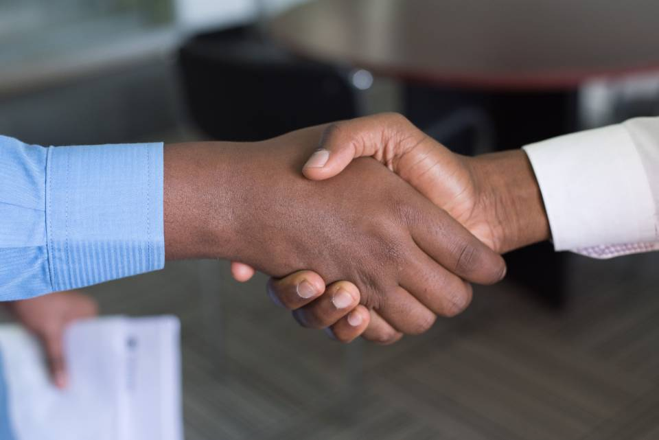 Two people shaking hands, potentially agreeing on a salary for a new employee