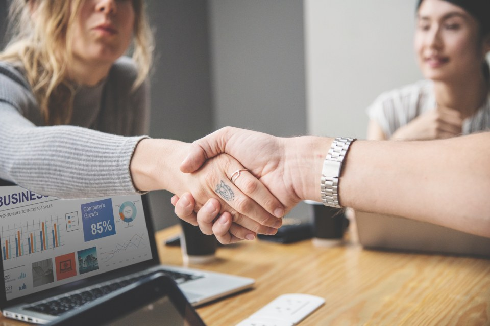 Two small business owners shaking hands while looking at a business plan