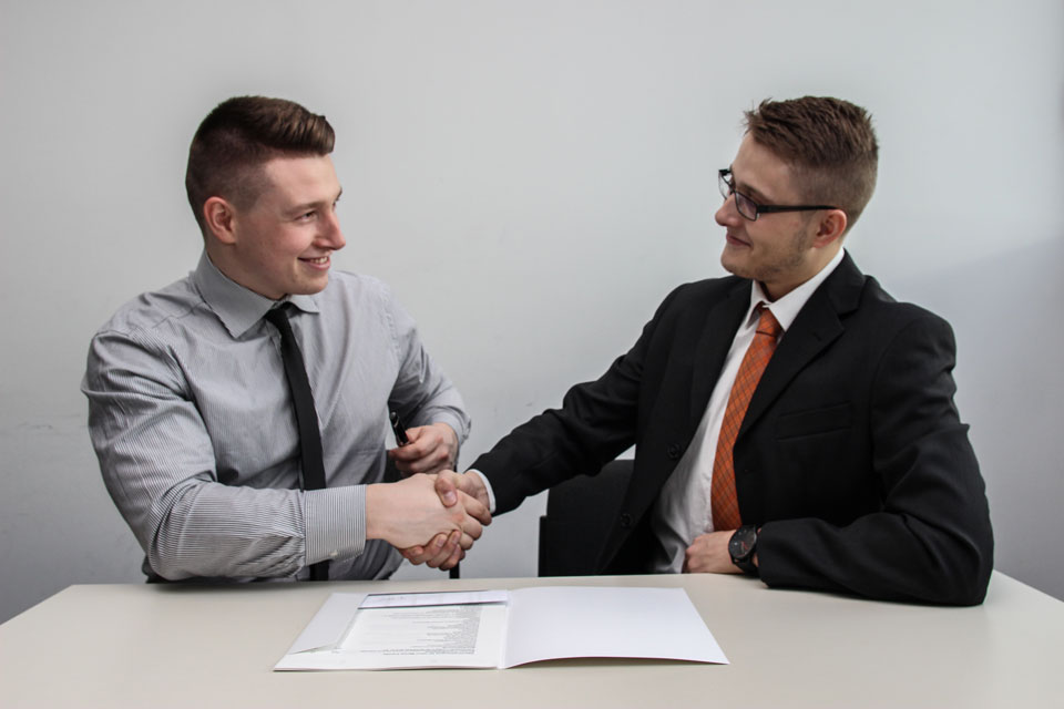 Two men in shirts and ties shaking hands over a document
