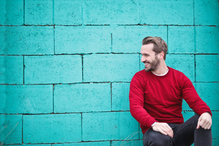 picture of bearded man smiling against a blue brick wall in a happy mood. Understand the mood of your customer when defining your audience